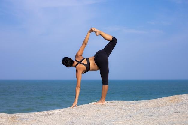 夏のビーチの夕日にアジアの妊娠中の女性のヨガ Premium写真