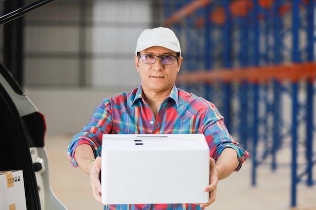 Азиатский человек доставляет хорошую коробку клиенту на фабрике и подписывает на планшете улыбку и хорошее обслуживание, концепция логистических покупок онлайн Premium Фотографии