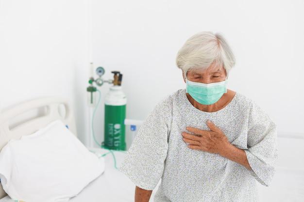 Азиатская старая терпеливая женщина с болезнью маски в палате с вирусным гриппом Premium Фотографии
