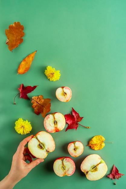 Осенняя тематическая плоская планировка из свежих половинок аплла и различных листьев, женская рука на зеленом фоне Premium Фотографии