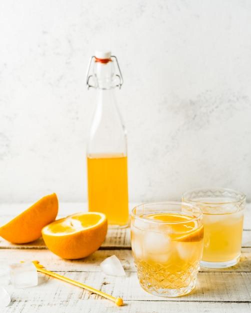 オレンジ色の夏の飲み物、白い背景の上に新鮮なオレンジ。縦画像 Premium写真