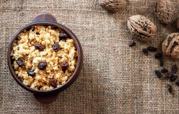 Сладкая пшенная каша с темным изюмом в керамической миске с грецкими орехами Premium Фотографии