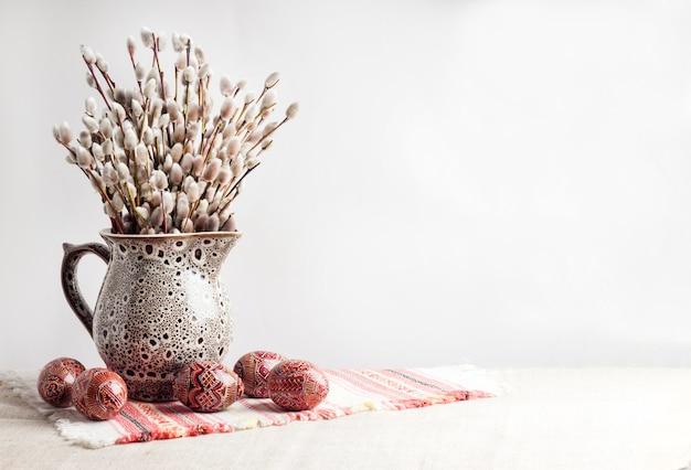 イースターの伝統的なウクライナの布にセラミックの水差しのピサンカと柳の枝のある静物。東ヨーロッパ文化の伝統的な装飾が施されたイースターエッグ Premium写真
