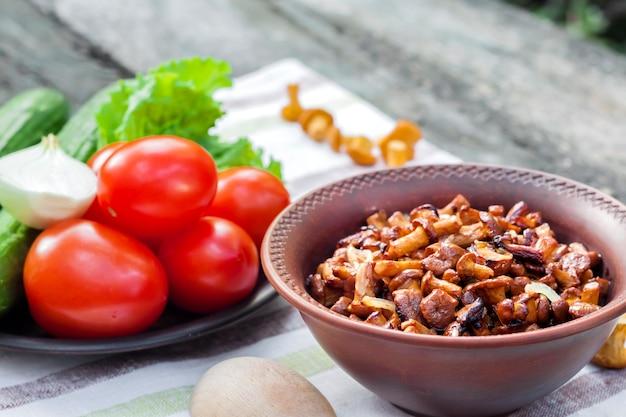 Жареные лисички с луком в деревенском миску и тарелку со свежими овощами для салата на фоне Premium Фотографии