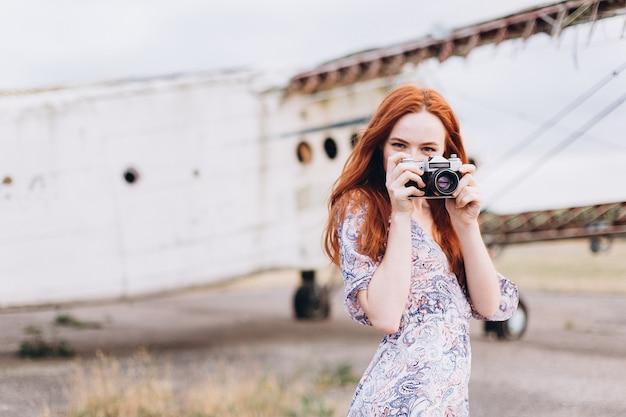 屋外で撮影するジンジャーガールカメラマン Premium写真