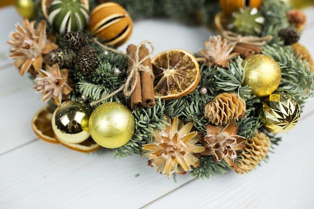 Новогоднее елочное украшение со специями, корицей, мандарином, канун на белом фоне деревянные Premium Фотографии