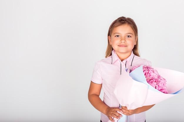 素敵なママの学校の先生のピンクの花の花束を持ってかわいい愛らしい女の子。 Premium写真