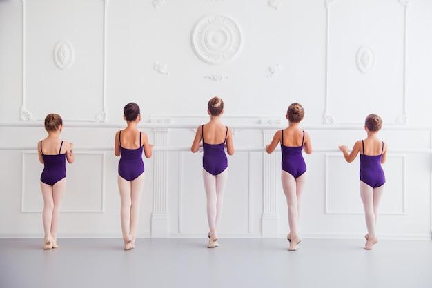 女の子はクラスの振り付けでバレエを行う Premium写真