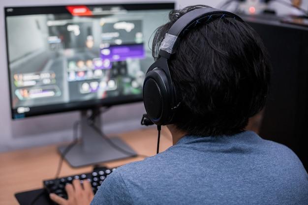 自宅でビデオゲームをプレイする若いゲーマーの背面図 Premium写真