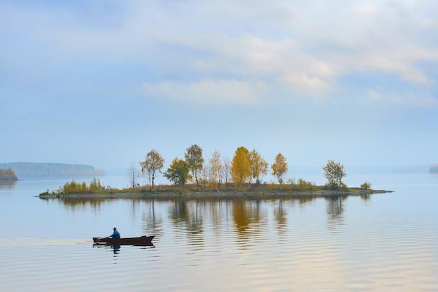 漁師は湖の島の周りを泳ぐ Premium写真