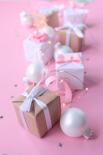 クリスマスの装飾とピンクの背景のギフトボックス Premium写真