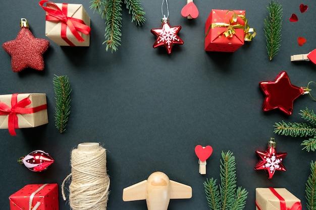 Новогоднее украшение с ветвями, звездами и подарочными коробками на черном фоне Premium Фотографии