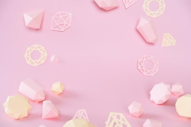 Разнообразные ограненные драгоценные камни, сделанные из бумаги на розовом фоне. Premium Фотографии
