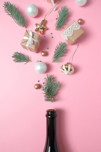 ピンクの背景に別のクリスマスの装飾とシャンパンのボトル。新年のコンセプト。 Premium写真
