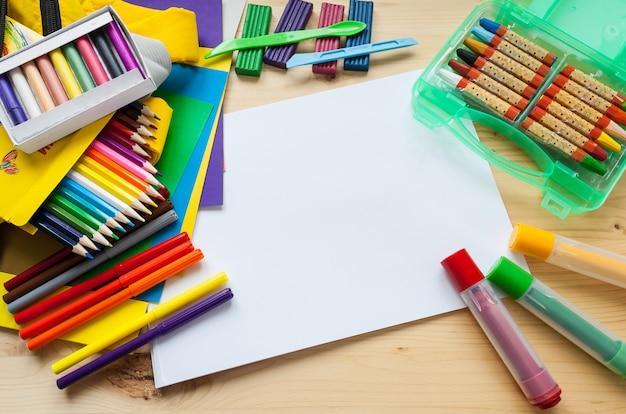 子どもたちの創造性。文房具フラットフレームはウッドの背景に置く Premium写真