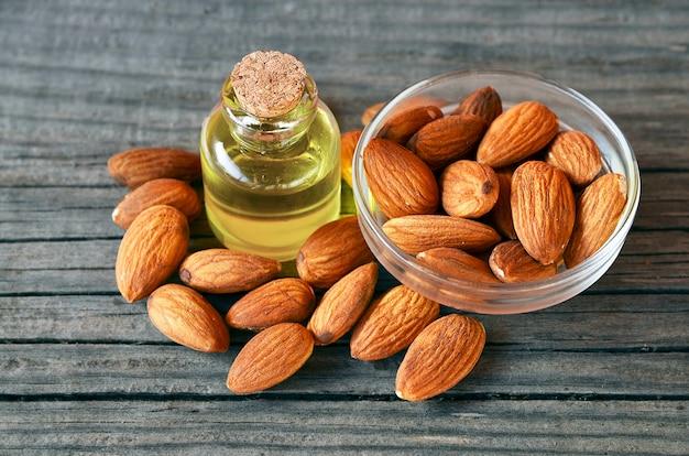 Семена миндалин и миндальное масло на старой деревянной предпосылке для здоровой еды, красоты и курорта. селективный фокус. Premium Фотографии