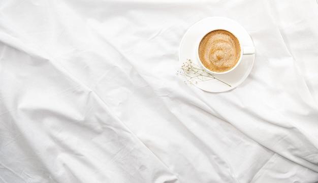 白いベッドで朝の平干し。コーヒーと朝のルーチン。 Premium写真