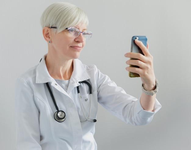 医師は携帯電話でビデオ通話をしています。ビデオ会議。診療所とオンライン患者受付 Premium写真