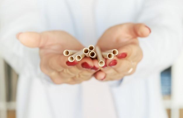 Женщина, держащая разлагающегося материала бумаги бамбука экологически чистых питьевой соломы. Premium Фотографии