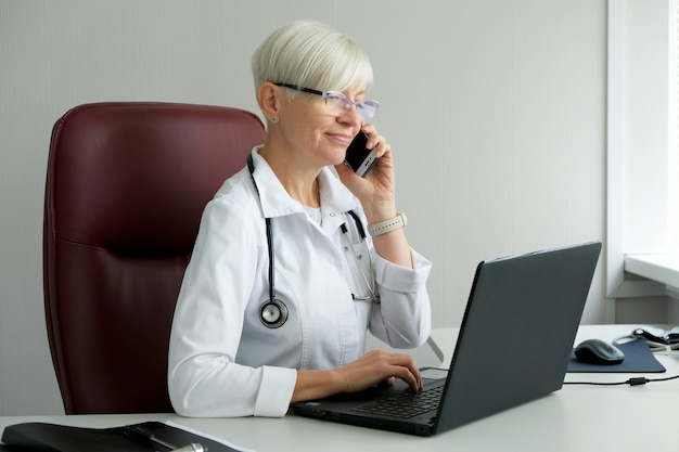 女医が診察室で電話で話しています。患者に相談します。 Premium写真