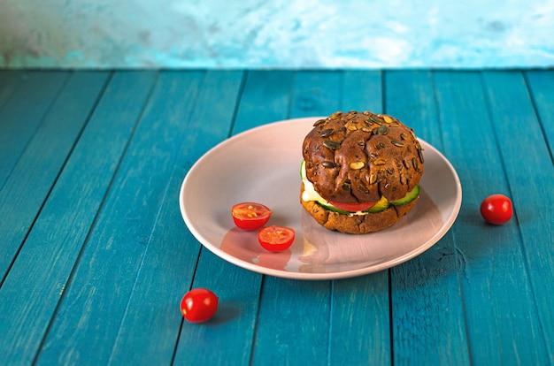 ヘルシーなビーガンバーガー、チーズ、キュウリ、トマトのプラトン、ヒマワリ、ゴマ、水色の木製テーブルの上のカボチャの種のパン Premium写真