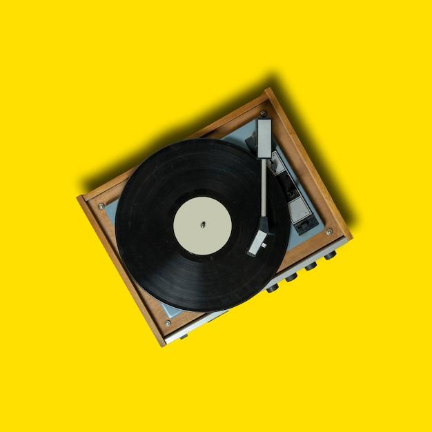 Старинный проигрыватель виниловых проигрывателей на желтом фоне. технология ретро-звука для воспроизведения музыки Premium Фотографии