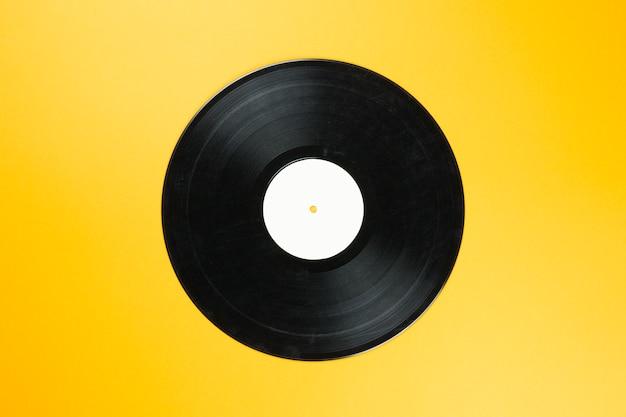 オレンジ色の背景の空の白いラベルを持つビンテージビニールレコードディスク。音楽を再生するレトロなサウンドテクノロジー Premium写真