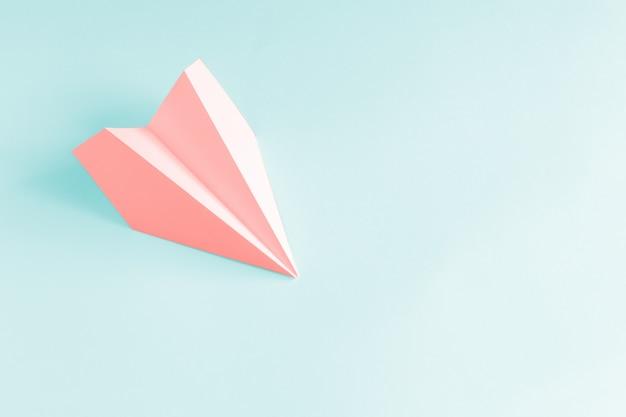 淡い青色の背景にサンゴ紙飛行機。 Premium写真