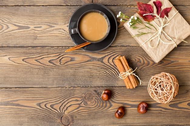 コーヒー、ミルク、ギフト、紅葉、シナモンスティック、木製の背景に栗。 Premium写真