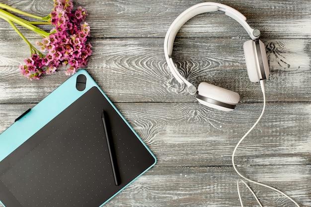Вид сверху на рабочем месте с цифровым планшетом и графическим пером, наушниками и цветком Premium Фотографии