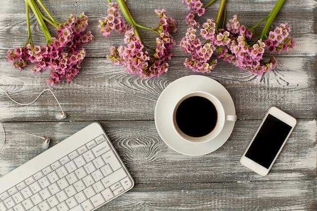 Взгляд сверху клавиатуры, наушников и чашки кофе, телефона и фиолетового цветка на сером деревянном столе. плоский дизайн. Premium Фотографии