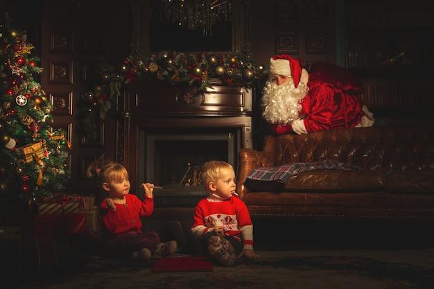 子供たちはクリスマスツリーの近くで遊ぶ。本当のサンタクロースは彼らを見ています。 Premium写真