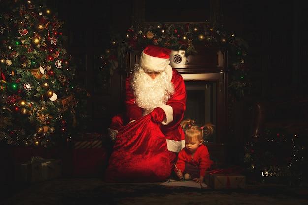 本物のサンタクロースは、クリスマスツリーの近くで子供たちと遊んでいます。 Premium写真