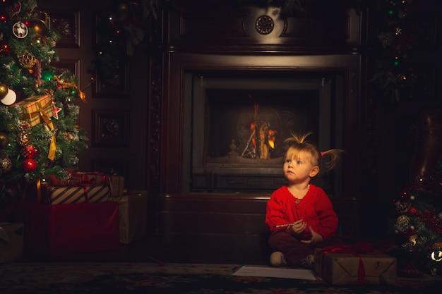 Маленькая милая девушка играет в гостиной возле елки. Premium Фотографии