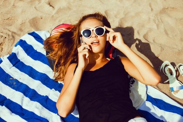 Девушка лежала на полотенце на пляже говорить на мобильный Premium Фотографии