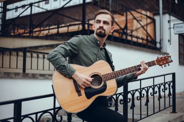 若いハンサムな男がギターを弾き、和音を拾い、ストリートミュージシャン 無料写真
