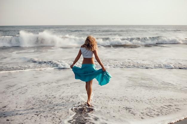 ビーチ、海、波、鮮やかな日差しと日焼けした肌でポーズを取る若い美しい少女 無料写真