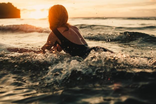 Молодая красивая девушка позирует на пляже с доской для серфинга, женщина-серфер, океанские волны Бесплатные Фотографии