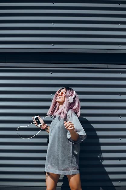 若い美しい女の子がストリートでスマートフォンを使用し、インターネットをサーフィンして音楽を聴く 無料写真