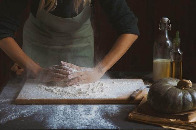 Женские руки замешивают тесто. выпечки ингредиенты на деревянный стол Premium Фотографии
