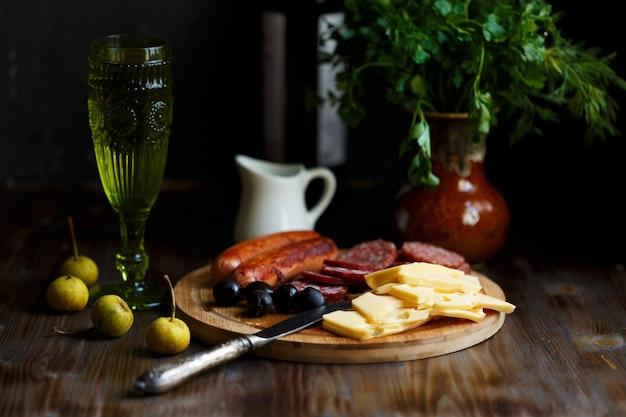 Аперитив столовый мясная закуска, жареные колбаски, сыр, салями, оливки и бокал вина на темном столе Premium Фотографии