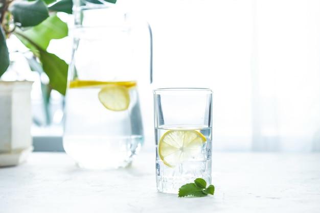 ガラスのコップの水、氷、ミント、レモンの白いテーブル Premium写真