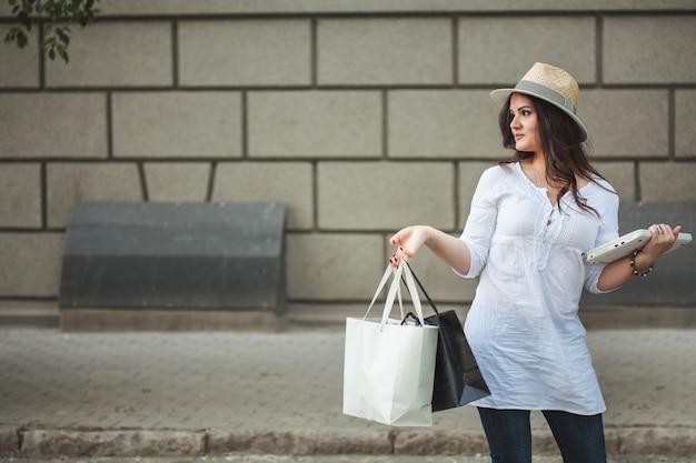 ノートパソコンと店からのパッケージが付いている通りを歩いて帽子の美しい笑顔ブルネットの少女。 Premium写真