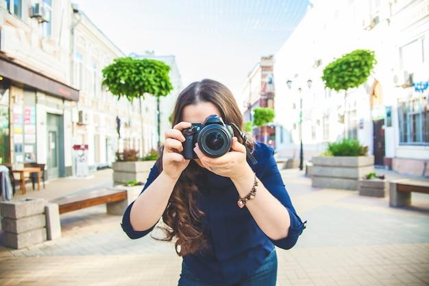 カメラで通りを歩いている美しい女性観光客と都市を探索するクローズアップを撮影しました。 Premium写真