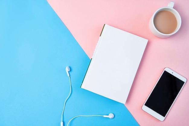 モックアップフラットは、青とピンクの背景にスマートフォン、ヘッドフォン、メモ帳、コーヒーカップとコンポジションを置きます。 Premium写真