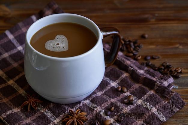 Чашка кофе с пеной в форме сердца. с любовью к кофе. на деревянном столе Premium Фотографии
