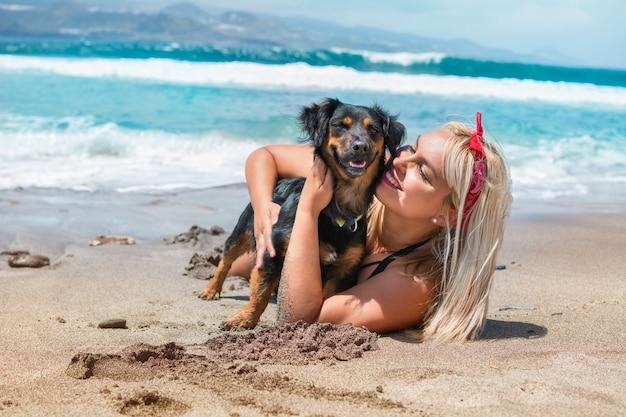 夏の日を楽しんでビーチで彼女の犬を抱いて美しい女性の肖像画 Premium写真