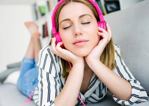 家庭で音楽を聴く美しい若い女性。 無料写真