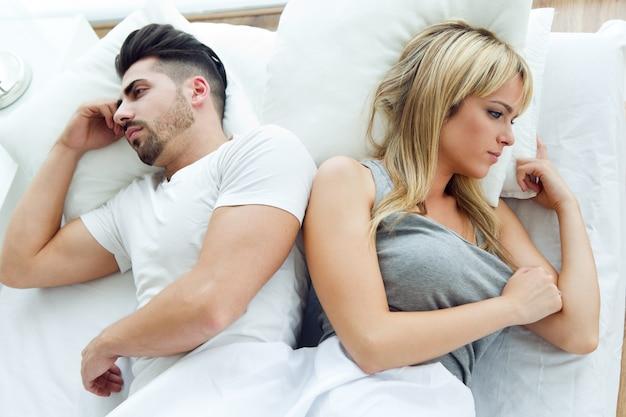 ベッドで背中合わせに横たわっている怒っているカップル 無料写真