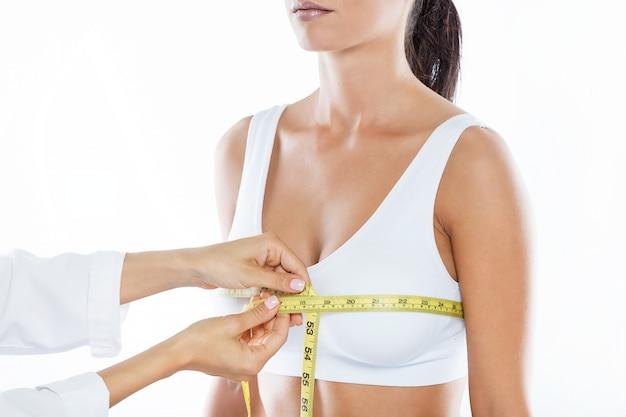 Врач с измерительной лентой, измеряющий размер груди пациента. Бесплатные Фотографии